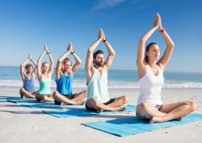People doing yoga on the beach
